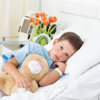 Kind mit Teddy im Spitalbett