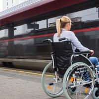 Symbolbild: Frau im Rollstuhl vor dem Zug – Bigstock